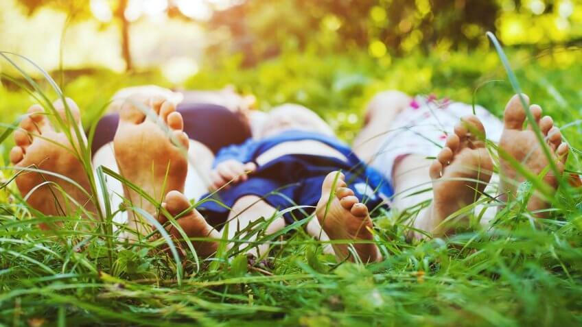 family laying in the grass at the part