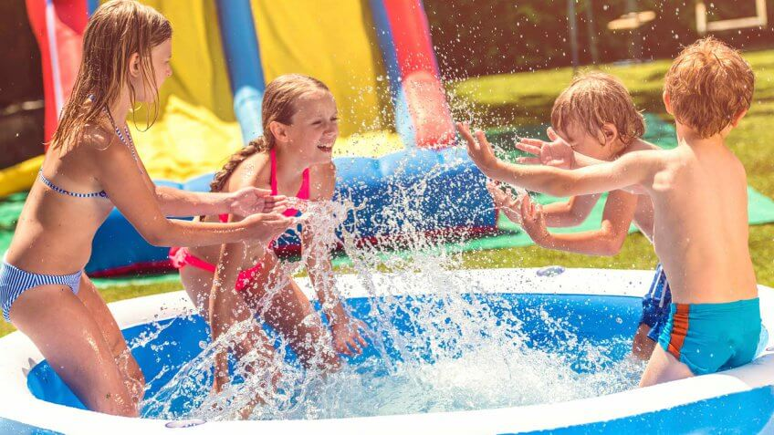 kids playing in an inflatable swimming pool