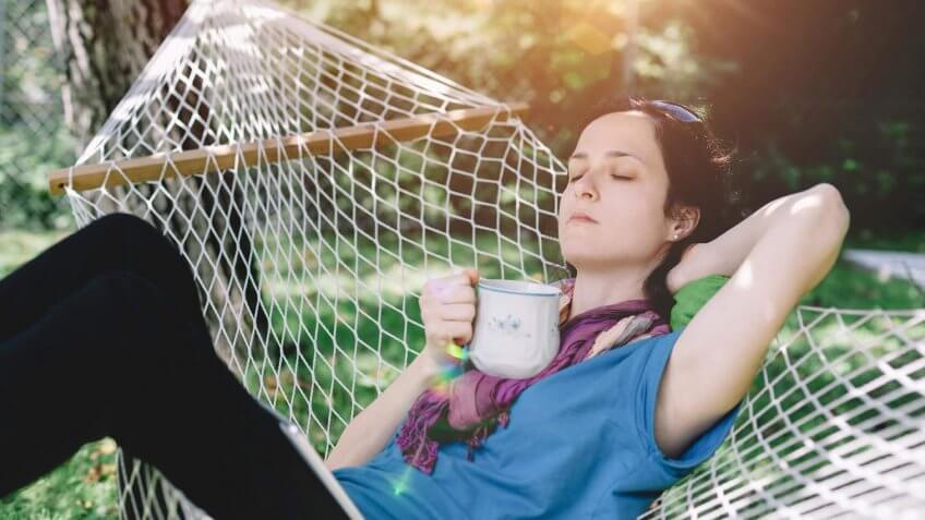 young woman sitting in a hammock drinking tea