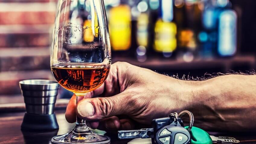 glass of alcohol next to a set of car keys