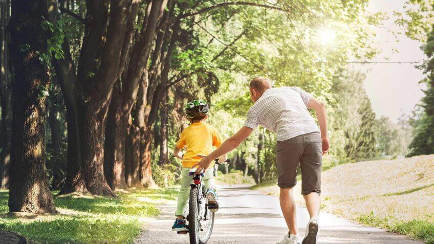 man teaching a child how to ride a bike