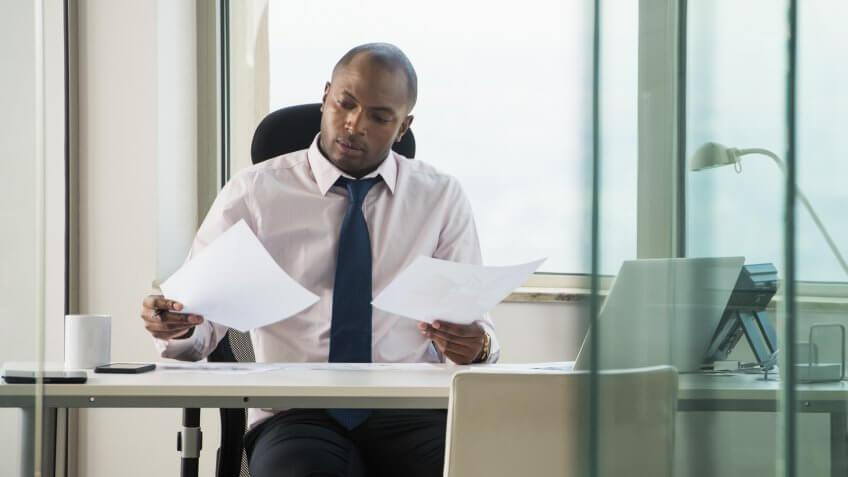 1 Person, 25-29 years, Adults Only, Business, Businessman, Businesswear, CEO, Concentration, Corporate, Desk, Document, Electric Lamp, Entrepreneur, Entrepreneurship, Examining, Executive, Male, Manager, Necktie, Nigerian, Office, One Man, Other Keywords, Shaved Head, Things to Know About High-Yield CDs, Transparent, Window, Work Environment, Working, Young Adult, Young Adult Man, african, african ethnicity, black, business attire, businessperson, coffee cup, communication, front view, glass, holding, indoor, indoors, laptop, mug, paperwork, professional, reading, shirt and tie, sitting, workplace, young man
