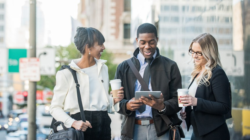 A young African American male and female and a young blonde caucasian female business associates or colleagues, on a coffee break, engaged in light-hearted conversation involving content on the digital tablet on the side of a city street.