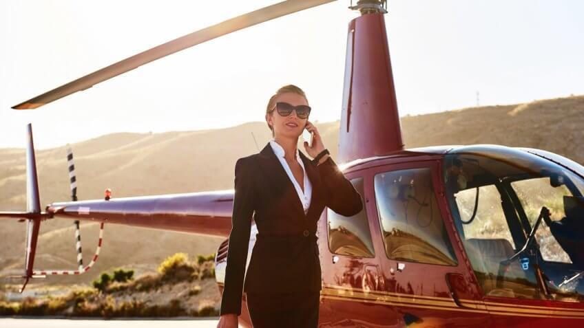 Elegant business woman talking by phone near the helicopter.