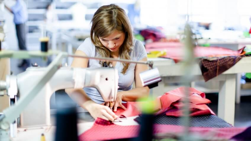 Young woman working in a clothes factory.