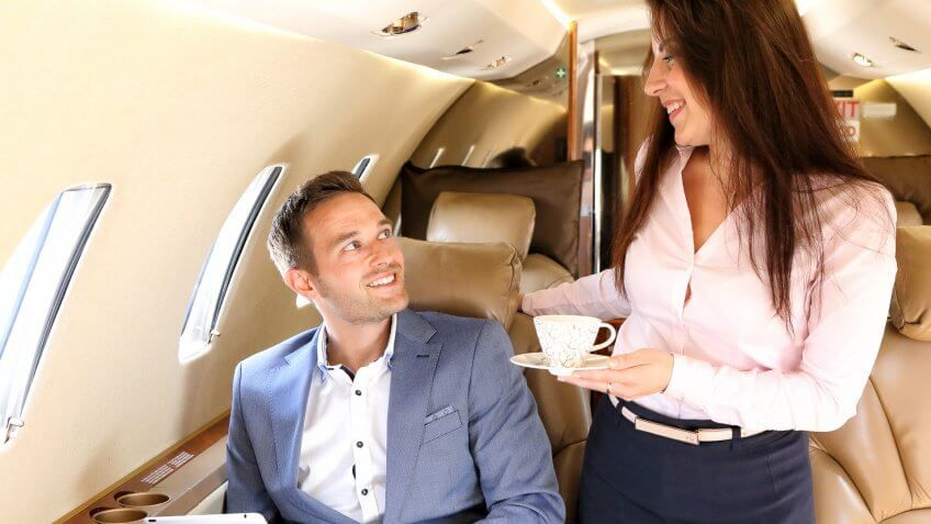 man being served coffee on a private jet