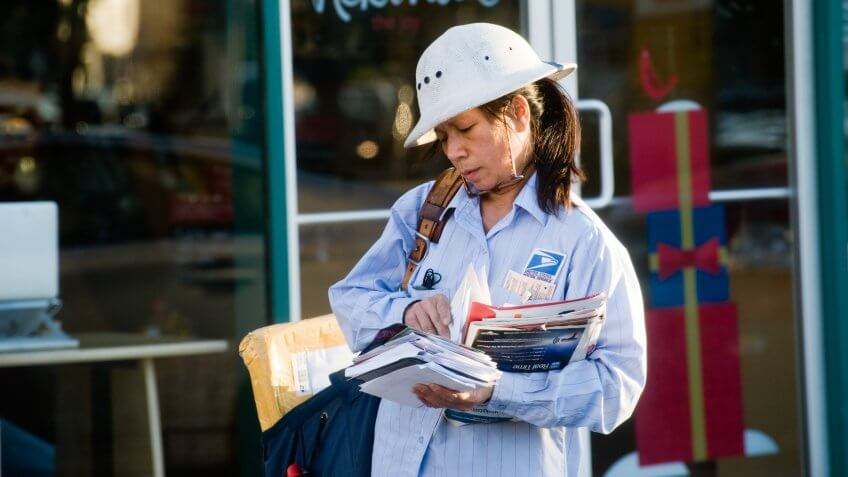 Los Angeles, California, USA - November 19, 2012: A mail carrier walks down a busy commercial and retail section of Santa Monica Blvd delivering letters and packages.