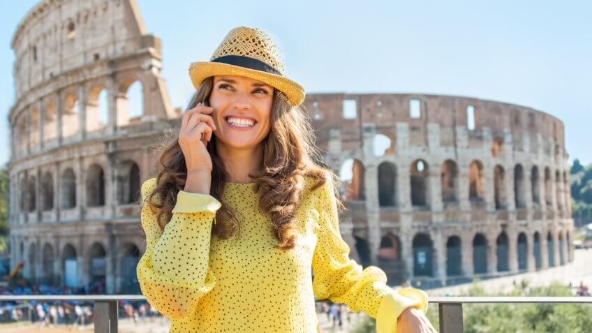 woman on her phone with the colosseum behind her