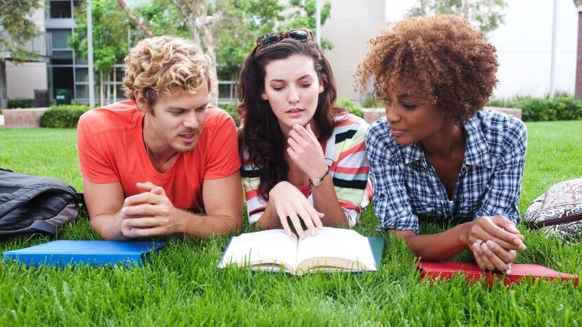 three friends laying on the grass reading a book