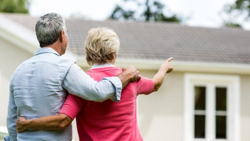 Rear view of senior couple looking at house while standing in yard.