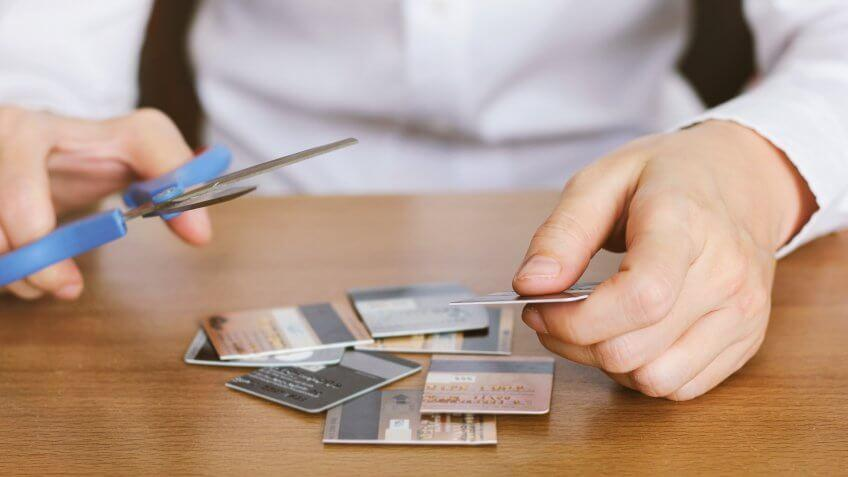 Person cutting credit cards using scissors