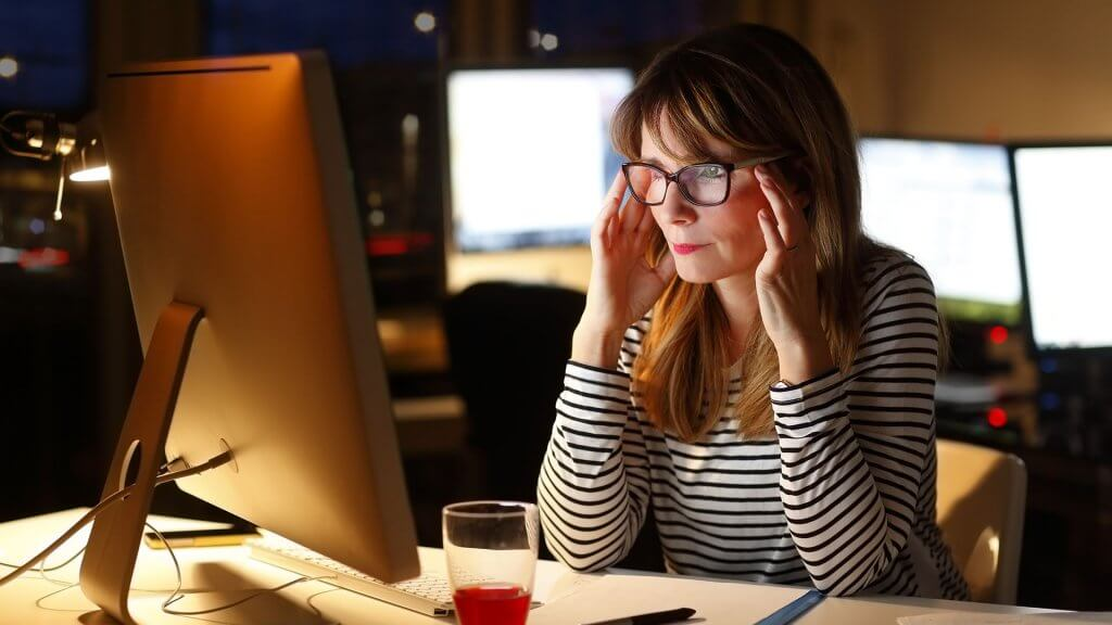 a stressed/focused woman working on an imac
