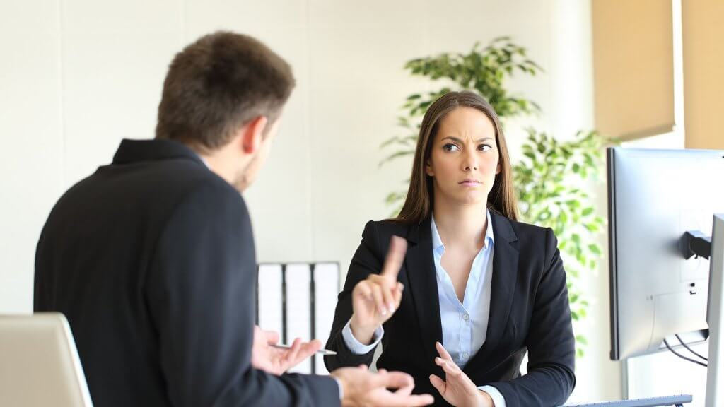 displeased businesswoman shaking finger at businessman
