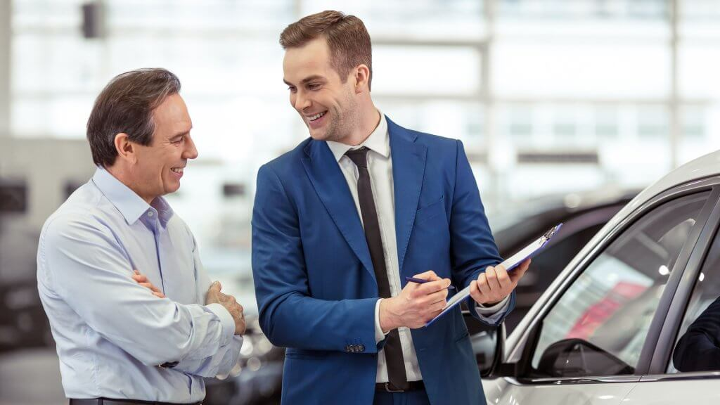 happy car salesman go over paperwork with customer
