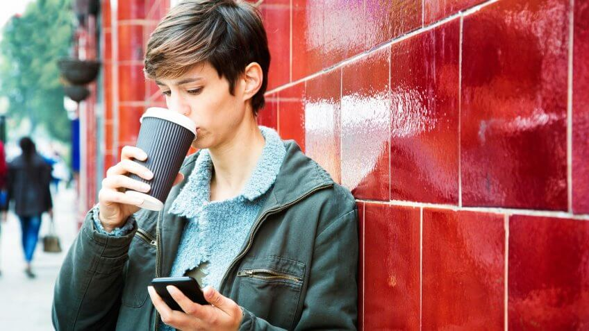 Stressed woman reading emails on her mobile phone with a frown while drinking coffee on her way to work.