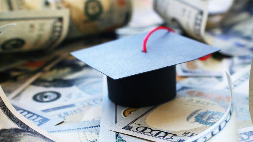 graduation cap on top of cash