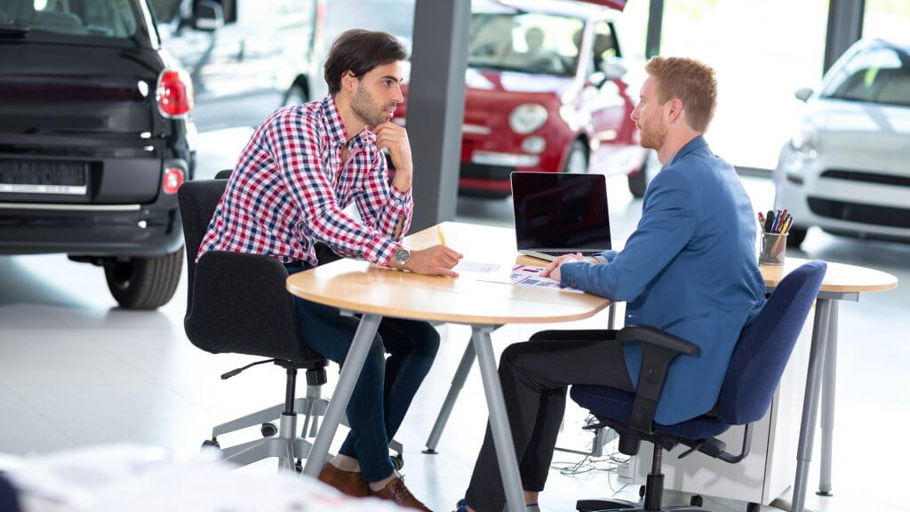 car salesman sitting at desk with customer