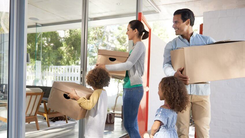 Shot of a young family moving into a new house with boxes in their hands.