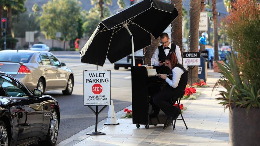 Palm Desert, United States - December 3, 2012: Two valet parking attendants in uniforms at a cubside kiosk in El Paseo Palm Desert.