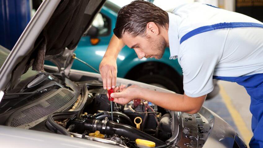 Repairman is working in repair shop.