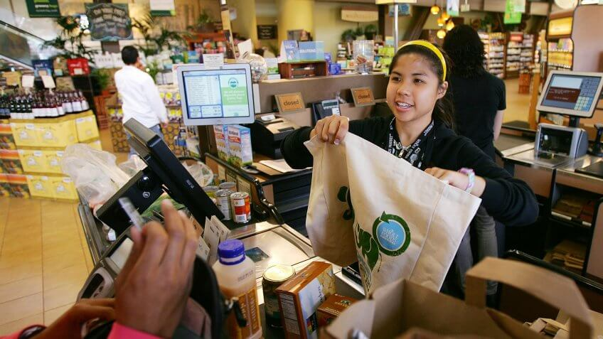 PASADENA, CA - APRIL 22:  Cashier Michelle Yulo hands out free reusable grocery bags at a Whole Foods Market natural and organic foods stores which is ending the use of disposable plastic grocery bags in its 270 stores in the US Canada and UK on Earth Day, April 22, 2008 in Pasadena California.