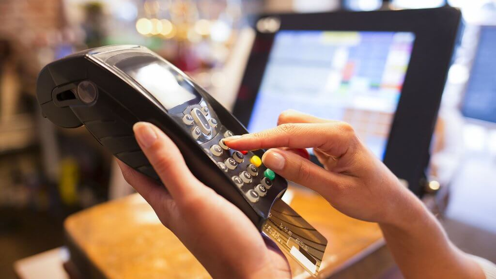 person typing pin into credit card reader