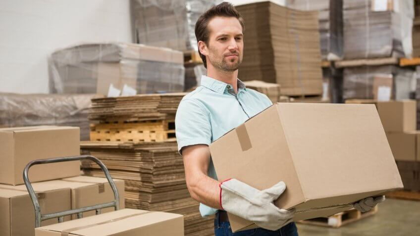 man carrying cardboard box in warehouse