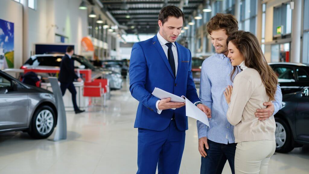 car salesman explaining paperwork to happy couple