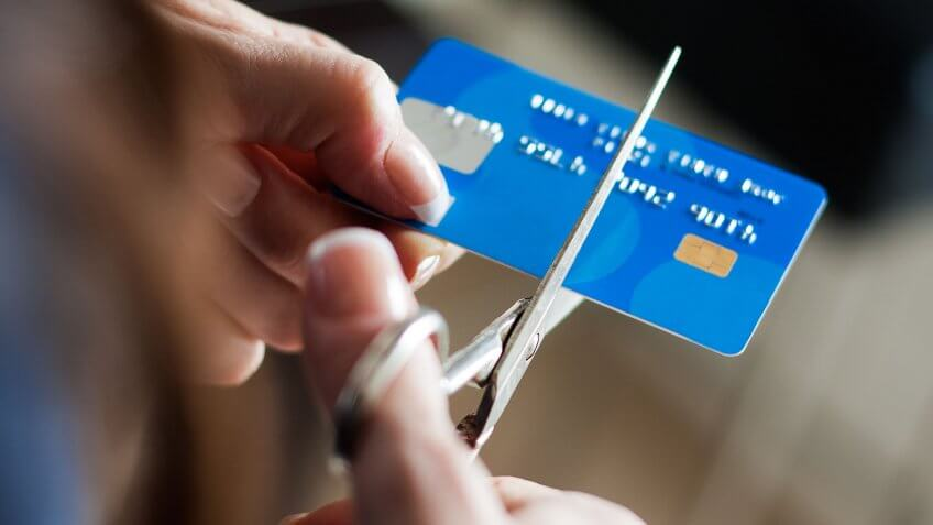 person cutting up credit card