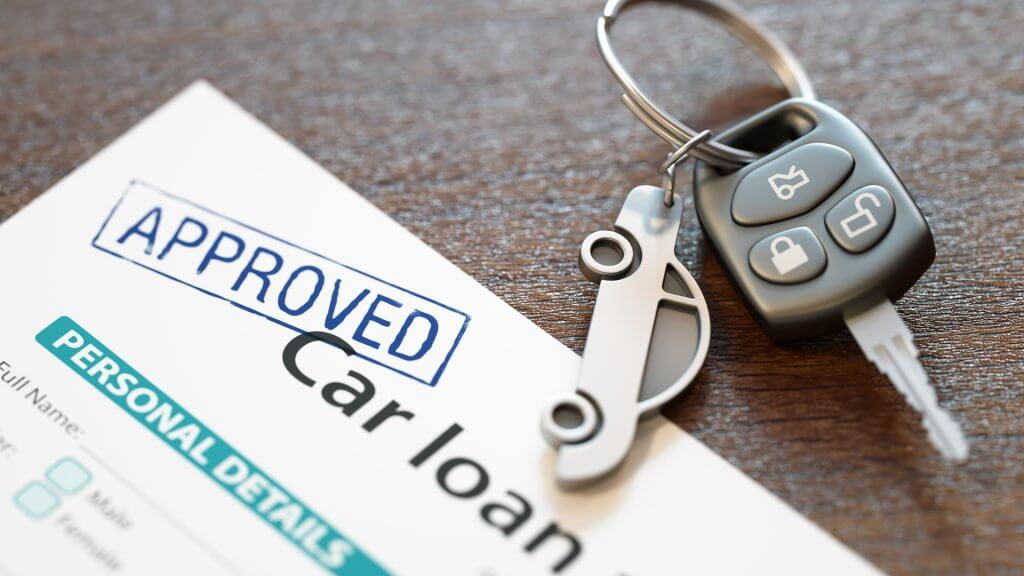 car keys laid on top of approved car loan document