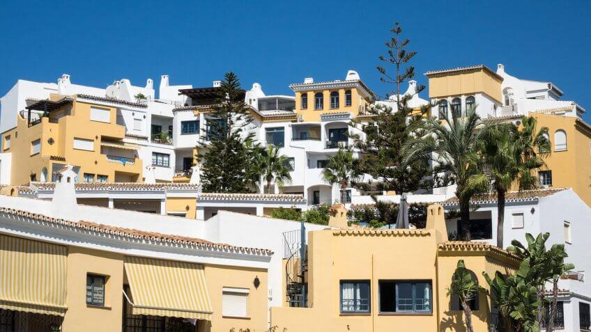yellow and white apartments with trees
