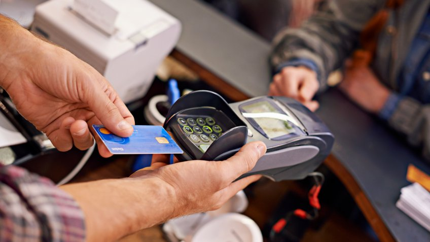Shot of a customer paying for their order with a debit machine in a cafehttp://195.