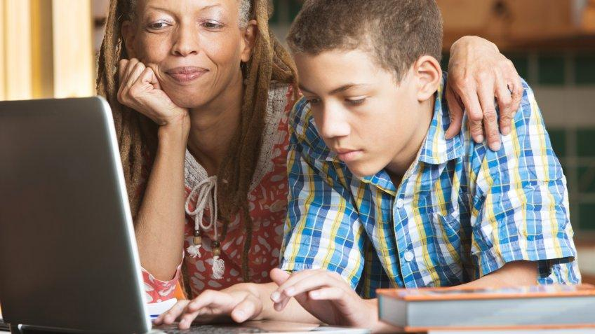 Mother overlooks as her teenaged son uses his laptop to study in their kitchen.