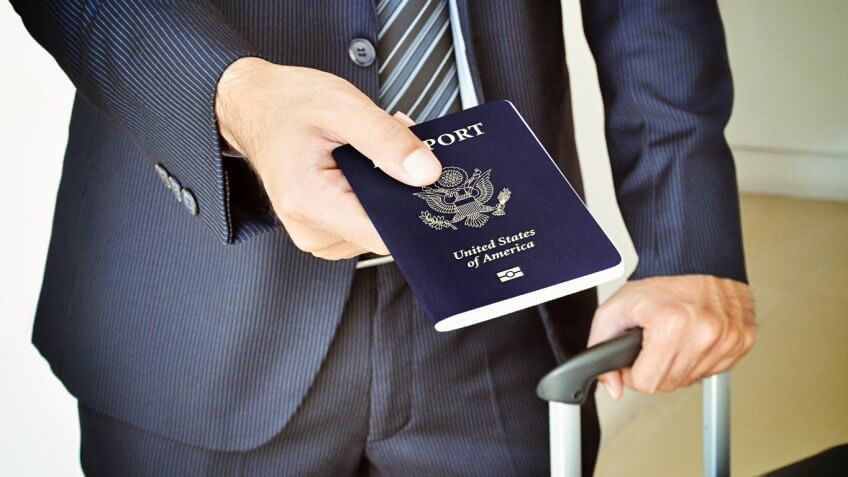 Man in suit handing over passport
