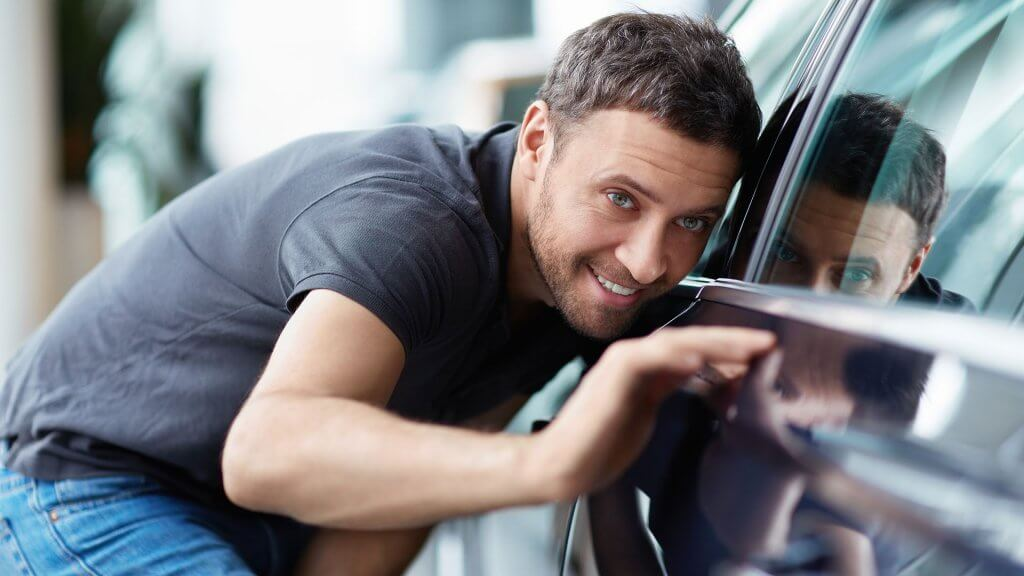 man inspecting side of car