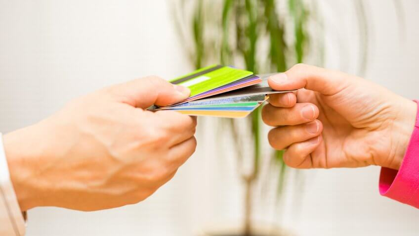 person handing stack of gift cards to person