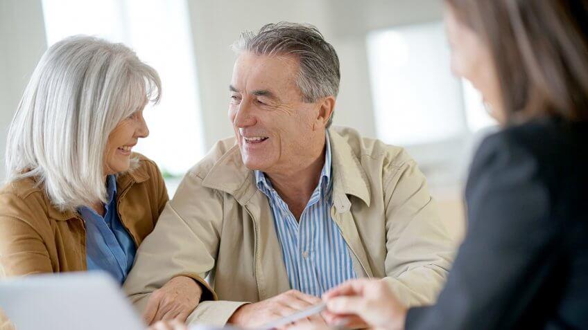 old senior retired couple talking to an adviser