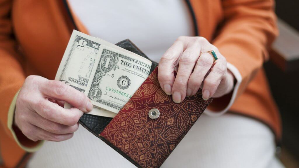 woman removing $6 from her purse