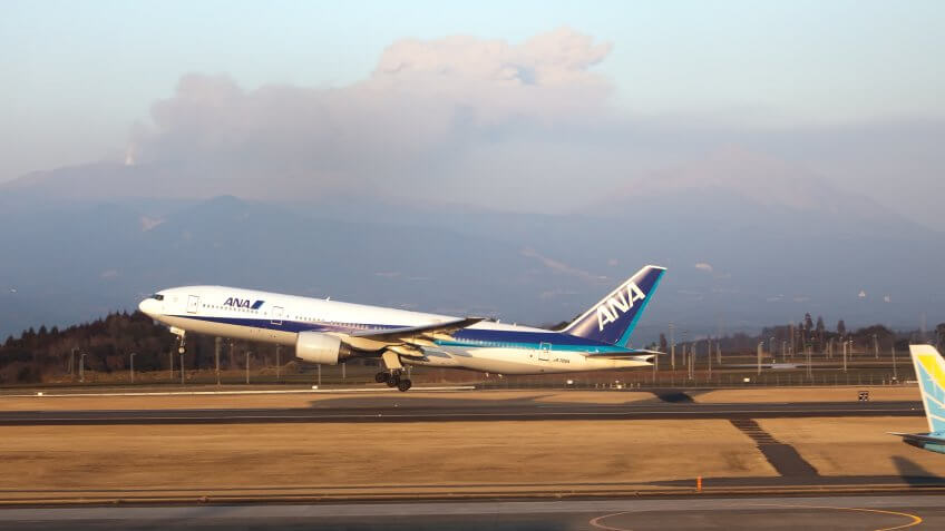 """Kagoshima, Japan - February 3, 2011: ANA airplane takes off with Shinmoedake volcano erupting in background."
