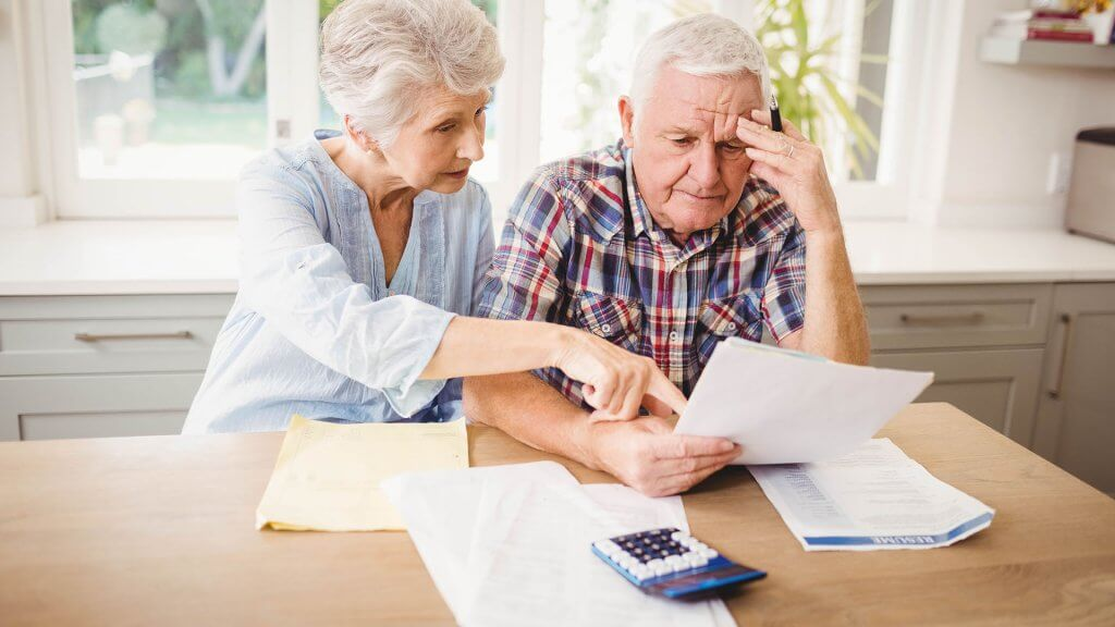 elderly couple looking over bills
