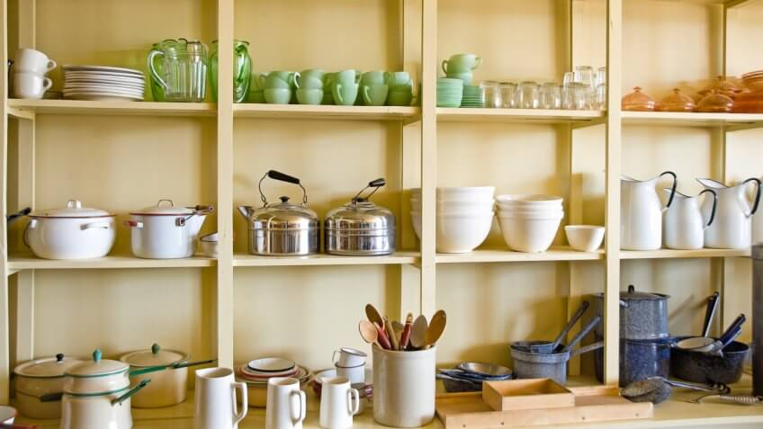 kitchen shelves with various pots, cups, plates and other kitchen items