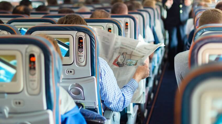 Person in airplane aisle seat reading a newspaper
