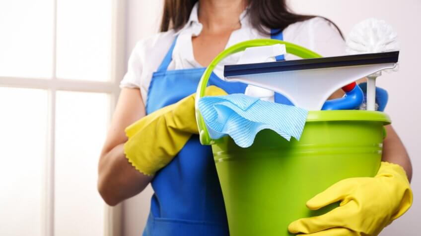 Woman in blue apron holding a green plastic bucket with cleaning tools