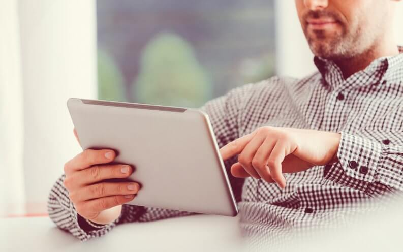 man using a digital tablet at home.