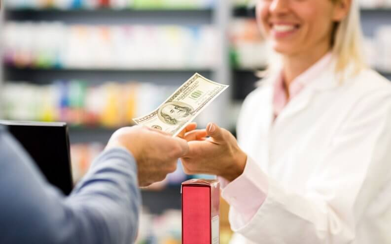 woman paying with cash in a pharmacy.