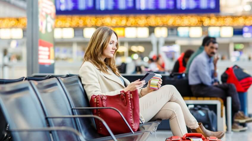 Woman reading on Kindle while waiting at airport