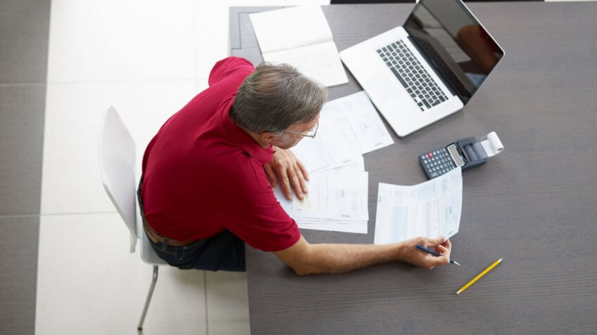 elderly man looking at document at desk