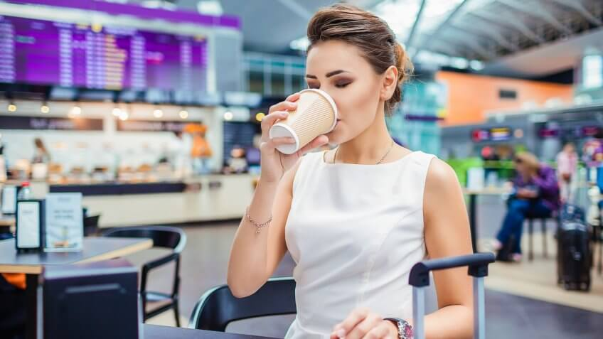 Woman sipping on coffee at airport cafe