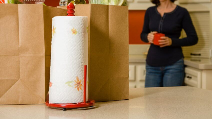 woman in kitchen with paper bags and paper towel roll on counter