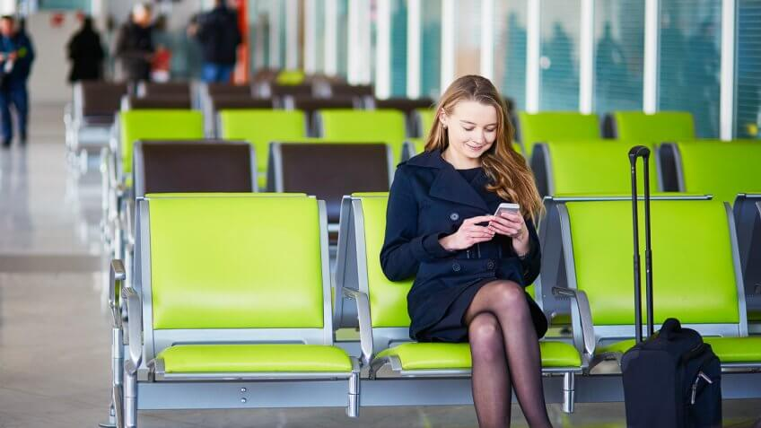 Woman sitting on airport chair checking phone